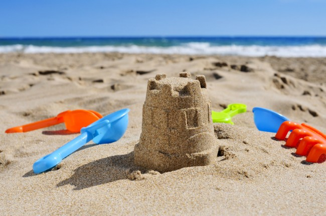 sandcastle and toy shovels on the sand of a beach
