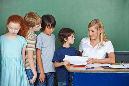 Lehrerin gibt Kindern Test zurück