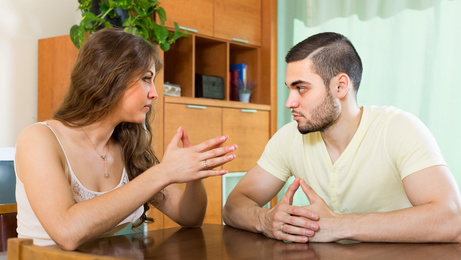 Serious young couple talking at home