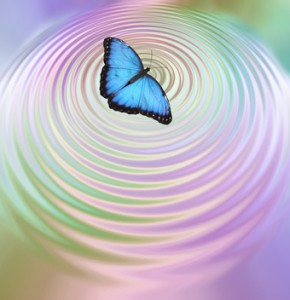 The Butterfly Effect - Big Blue Butterfly appearing to create ripples in pink green water surface with plenty of copy space below